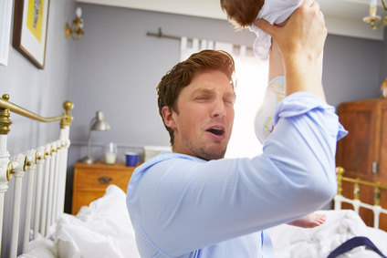 Father Dressed For Work Changing Baby's Diaper In Bedroom
